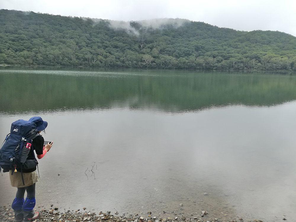 小沼で写真撮影する人